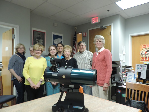 Friends of HPL standing behind library telescope